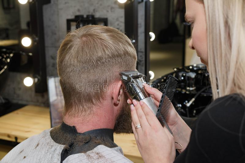Barber hair cutting machine. The master provides a haircut. Barber cutting hair with clipper. Master provides service. The master makes a haircut with a machine stock image