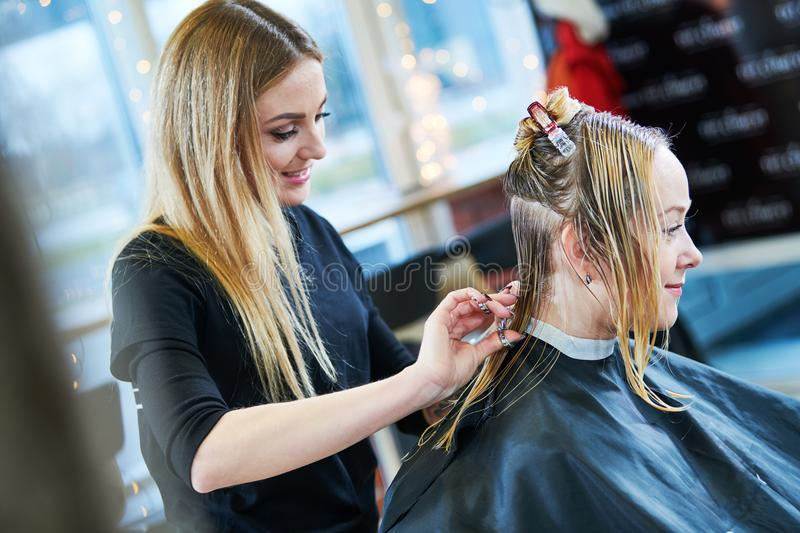 Barber or stylist at work. Hairdresser cutting woman hair stock photography