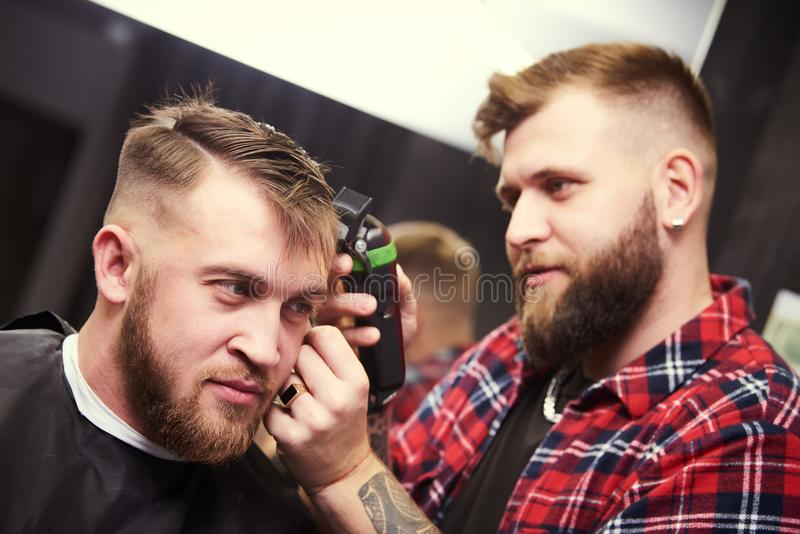 Barber or hair stylist at work. Hairdresser cutting hair of client stock photography