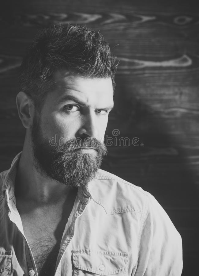 Barber and hairdresser salon. Man with beard and mustache on wooden background. Haircut of bearded man, archaism. Serious hipster in barbershop, look. Fashion stock photos