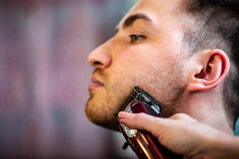 Barber make beard haircut with trimmer hair clipper in barbershop. Hairstyle in male hair salon.  stock photo