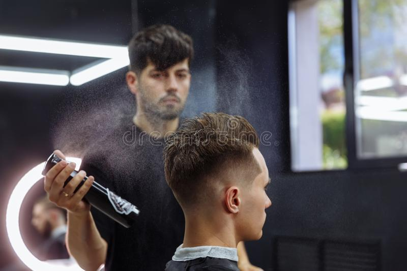 Barber makes hair styling with hair spray after haircut at the barber shop. Young handsome Caucasian man getting a royalty free stock images