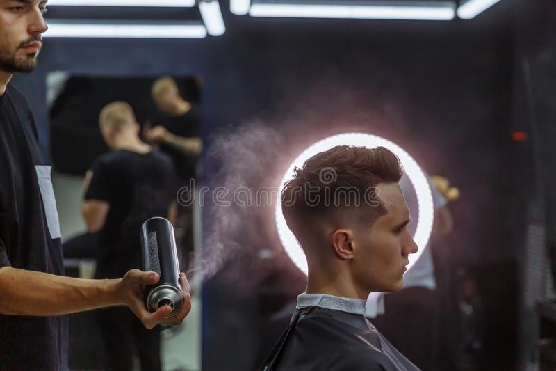Barber makes hair styling with hair spray after haircut at the barber shop. Young handsome Caucasian man getting a. Barber makes hair styling with hair spray royalty free stock image