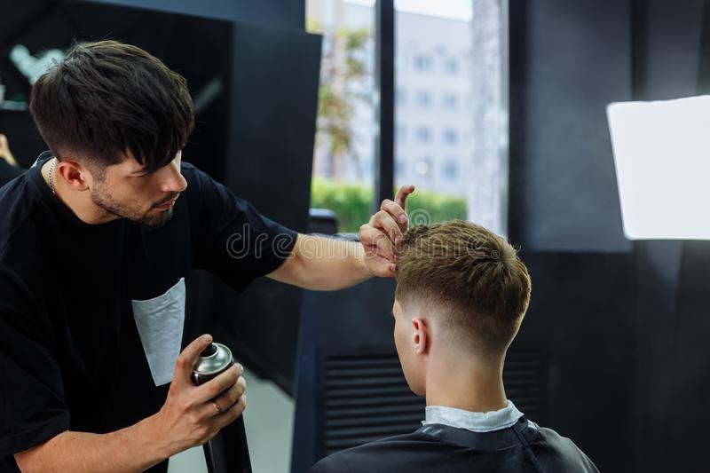 Barber makes hair styling with hair spray after haircut at the barber shop. Young handsome Caucasian man getting a. Barber makes hair styling with hair spray royalty free stock images