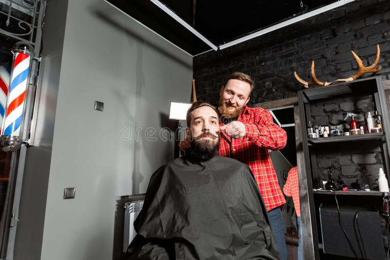 Barber is making the beard shape. Beard cutting, face care. Work in barber shop. royalty free stock photos