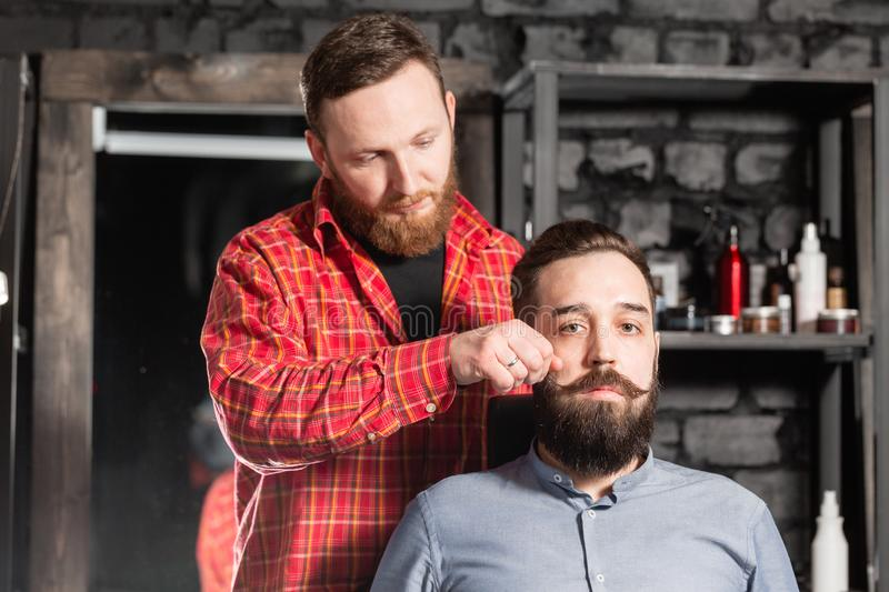 Barber is making the beard shape. Beard cutting, face care. Work in barber shop. royalty free stock photography