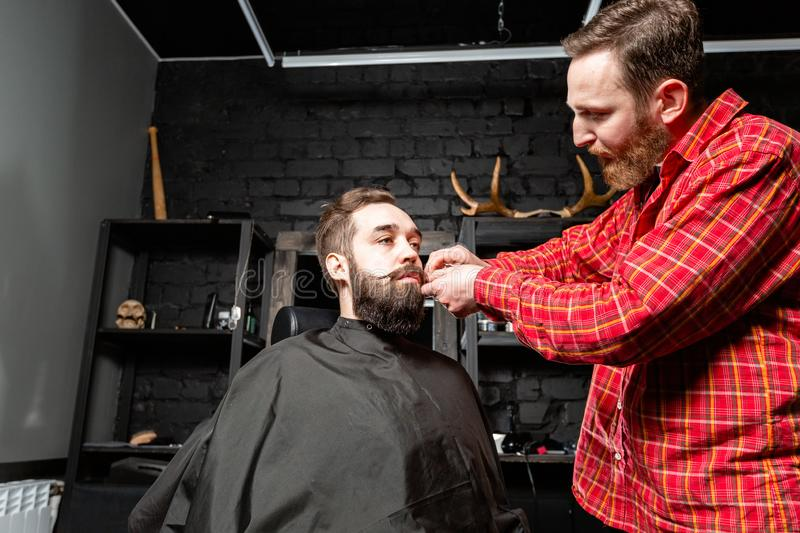 Barber is making the beard shape. Beard cutting, face care. Work in barber shop. stock photos