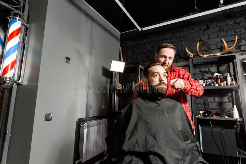 Barber is making the beard shape. Beard cutting, face care. Work in barber shop. stock photography