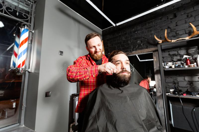 Barber is making the beard shape. Beard cutting, face care. Work in barber shop. stock image