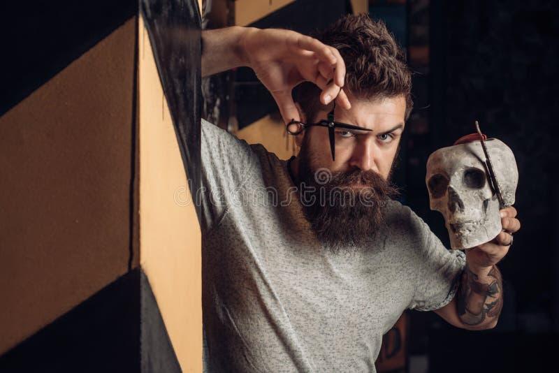 Barber making haircut of attractive bearded man in barber shop. Vintage barber shop shaving. Bearded man getting haircut. By hairdresser at barbershop. Razor stock photo