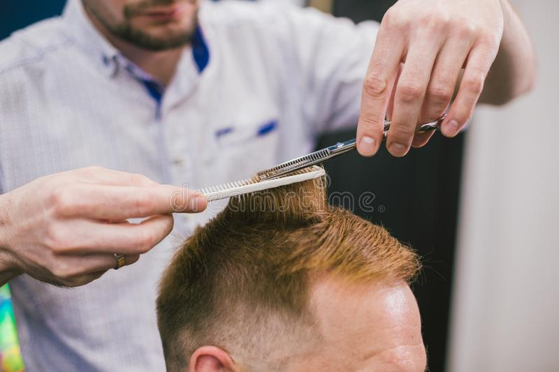 Barber Making Haircut Bearded Man In Barbershop. Professional stylist cutting client hair in salon. Barber using royalty free stock images