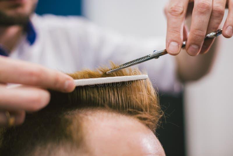 Barber Making Haircut Bearded Man dans le raseur-coiffeur Cheveux professionnels de client de coupe de styliste dans le salon Uti photographie stock libre de droits