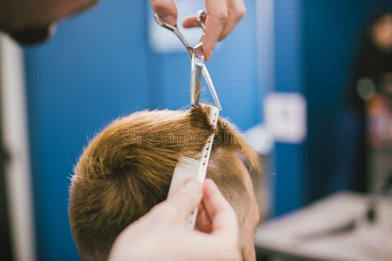 Barber Making Haircut Bearded Man in Herenkapper Het professionele haar van de stilist scherpe cliënt in salon Kapper het gebruik royalty-vrije stock foto