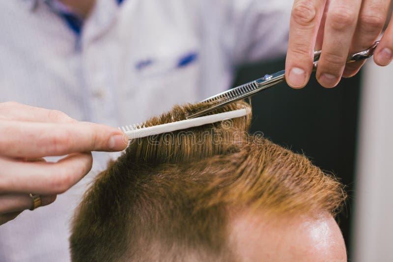 Barber Making Haircut Bearded Man in Herenkapper Het professionele haar van de stilist scherpe cliënt in salon Kapper het gebruik royalty-vrije stock foto's