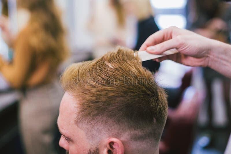Barber Making Haircut Bearded Man i frisersalong Yrkesmässigt hår för stylistklippklient i salong Använda för barberare royaltyfri fotografi