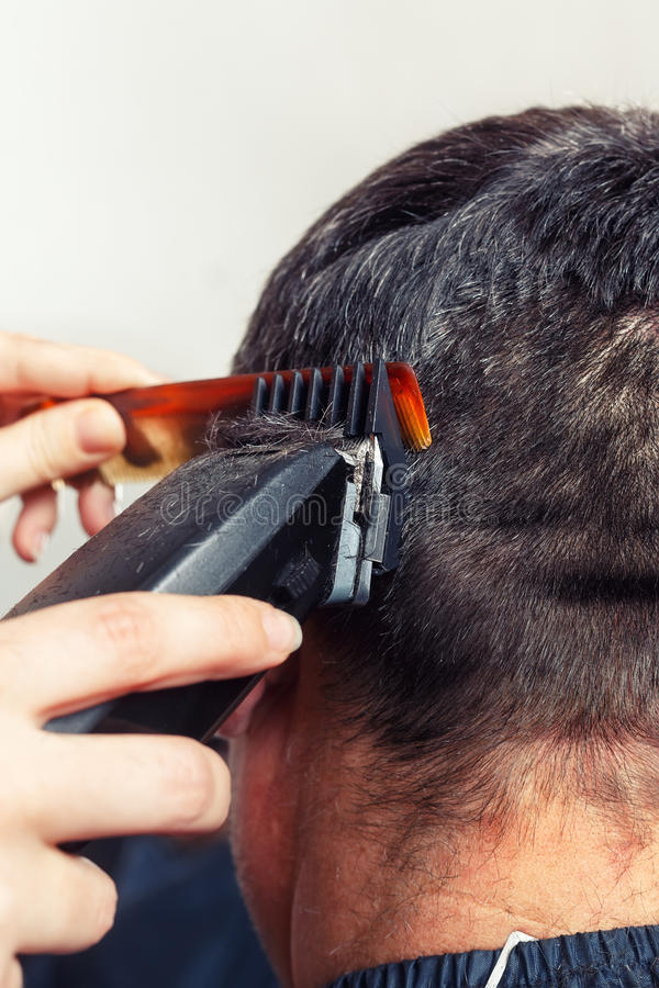 Barber making haircut. Brunette man getting a haircut by a professional hairdresser using comb and grooming machine. Closeup man having a haircut with a hair stock image