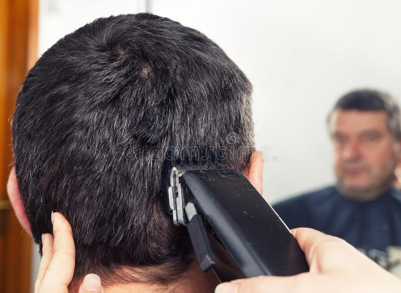 Barber making haircut to man. Man getting a haircut by a professional hairdresser using grooming machine. Closeup man having a haircut with a hair clippers. The royalty free stock photo