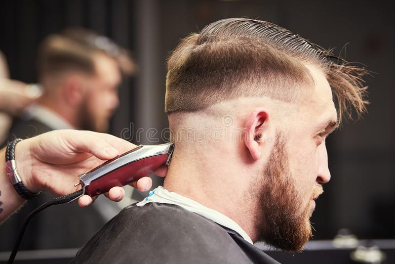 Barber making male haircut. Hairdresser cutting hair of client royalty free stock photography