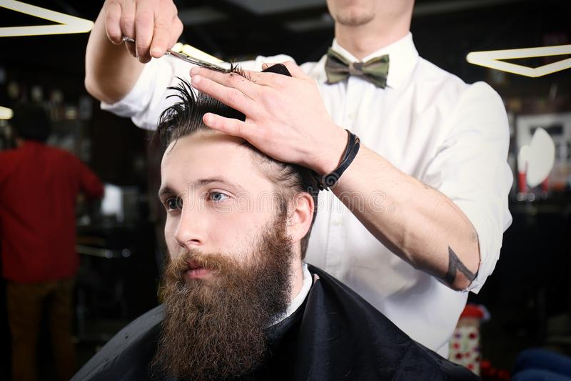 Barber making modern hairstyle stock photos