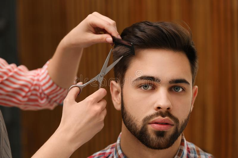 Barber making stylish haircut with professional scissors stock image