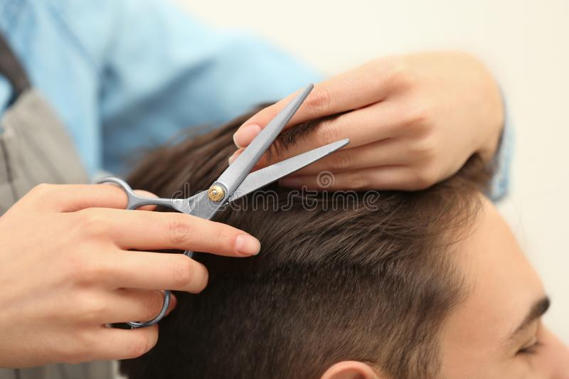 Barber making stylish haircut with professional scissors in beauty salon stock photo