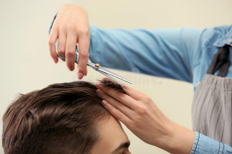 Barber making stylish haircut with professional scissors in beauty salon stock image