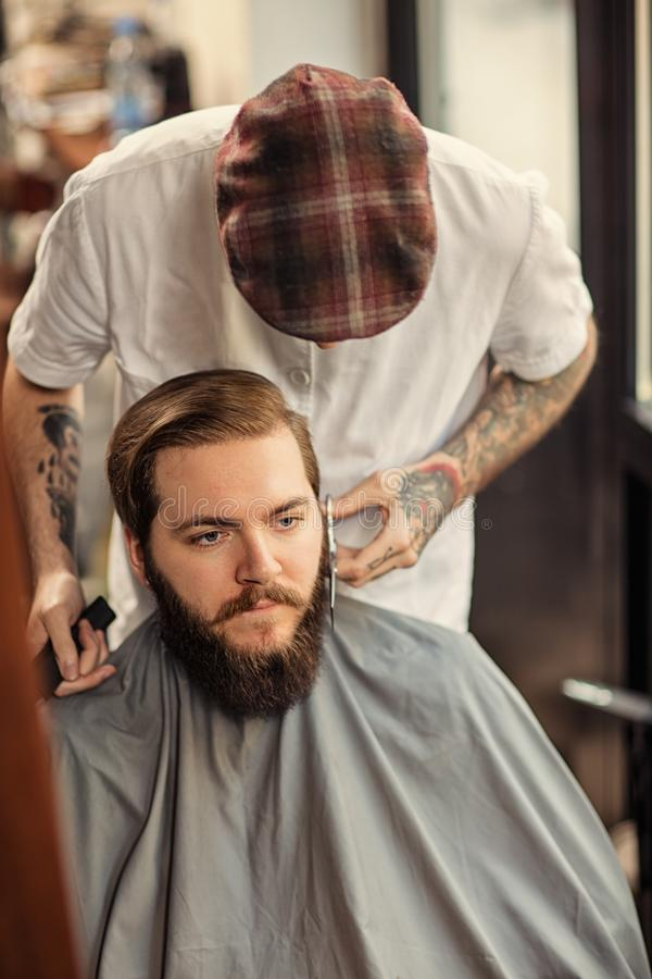 Barber man grooming with scissors of real hipster stock photography
