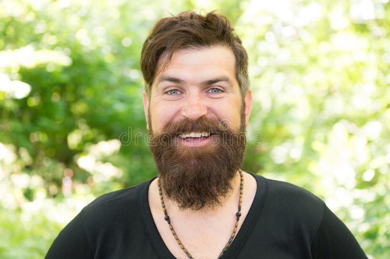 Barber obsessing about his hair. Bearded man with shaped beard and mustache hair smiling before or after visiting barber. Happy barber on natural landscape. A stock image