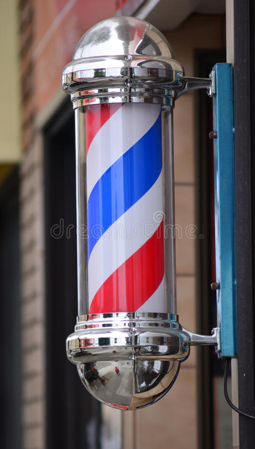 Barber pole sign. American barber pole sign with a helical stripe (red, white, and blue ) on a wall of a Barber's shop royalty free stock image