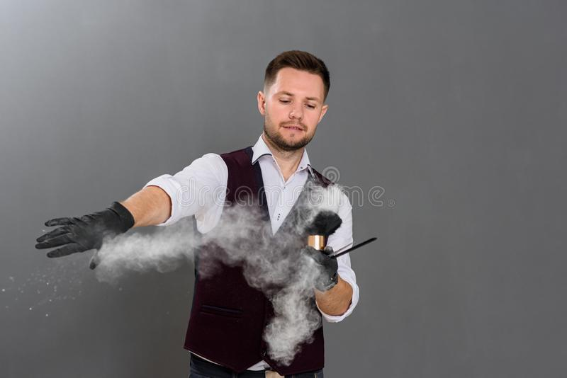 Barber posing in studio and spilling powder with brush in air. stock photography