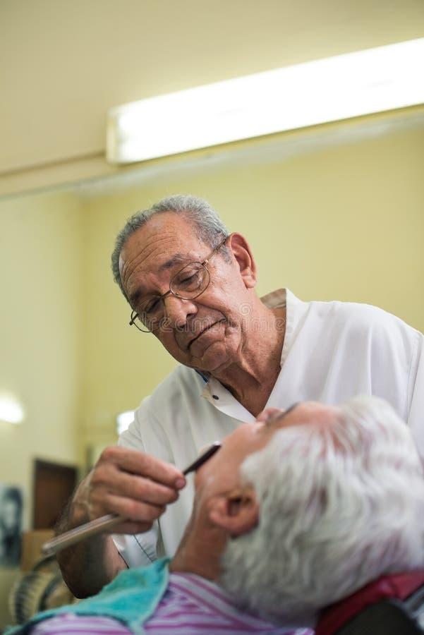 Barber with razor shaving client in barber shop