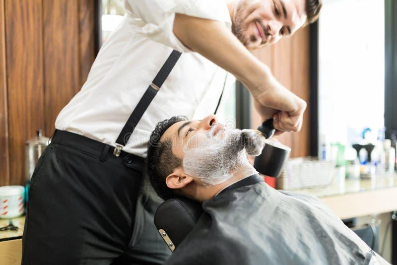 Barber Rubbing Shaving Foam On-Cliënt` s Gezicht met Borstel royalty-vrije stock afbeelding