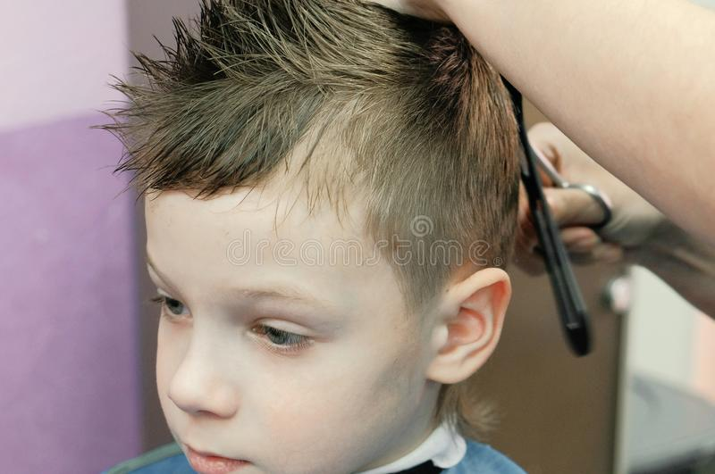 Barber`s hands combs and cutting blond short boy`s hair with scissors. Closeup boy`s face. Barber`s hands combs and cutting blond short boy`s hair with scissors royalty free stock images
