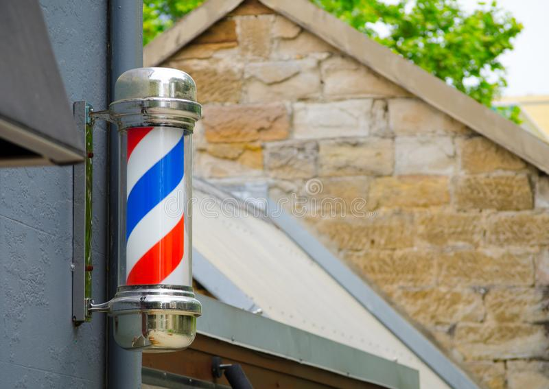 Barber`s pole sign attached on the wall in front of a Barber shop. royalty free stock images