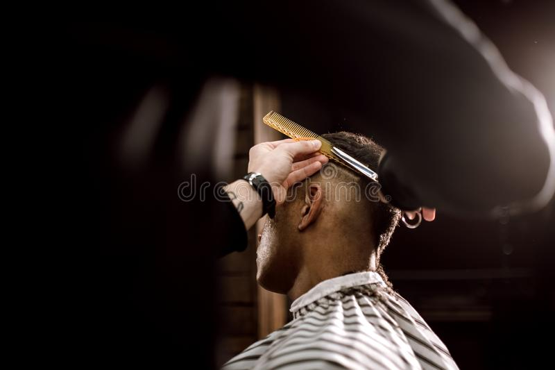 The barber scissors hair on the sides for a stylish black-haired man in the barbershop. Men`s fashion and style royalty free stock photos