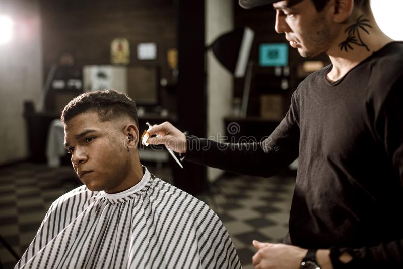 The barber scissors hair on the sides for a stylish black-haired man in the barbershop. Men`s fashion and style. The barber scissors hair on the sides for a stock images