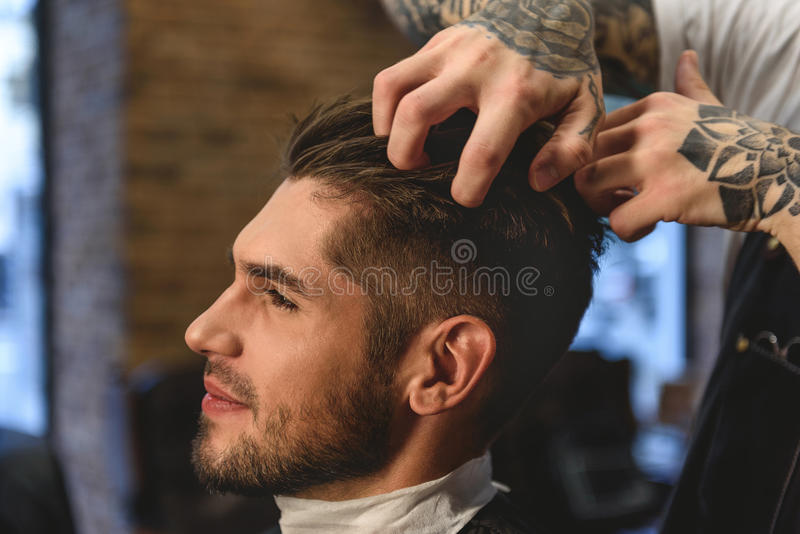 Barber scratching head of a customer. Side view of a stylist playing with hairs of sitting man stock photos