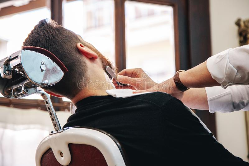 Barber sharpens an old razor in the traditional way stock photos
