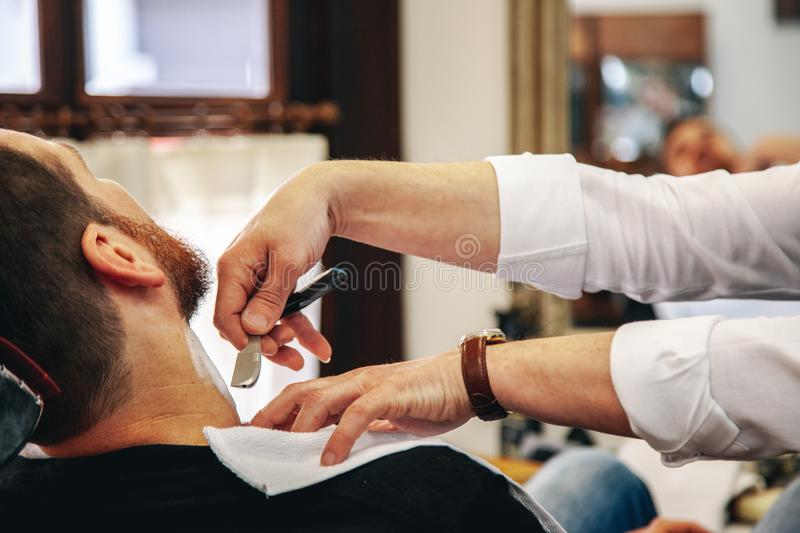 Barber sharpens an old razor in the traditional way royalty free stock photography