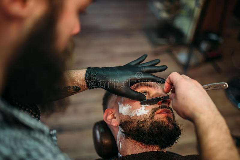 Barber shaves beard of the client at barbershop royalty free stock photo