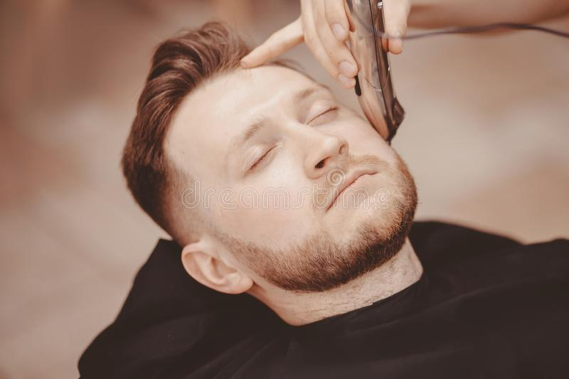 Barber shaves beard of client man on chair Barbershop stock image