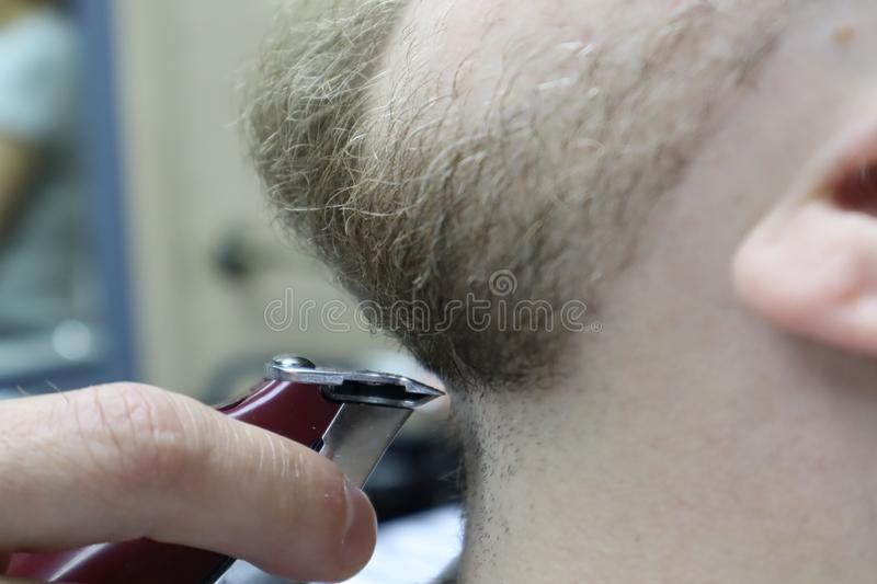 Barber shaves beard of client man on chair Barbershop. Beard Haircut. barber shaving beard with electric razor in vintage barber s stock photography