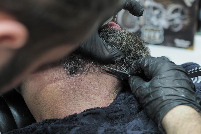 Barber shaves the beard of an elderly man with gray hair sharp razor stock photos