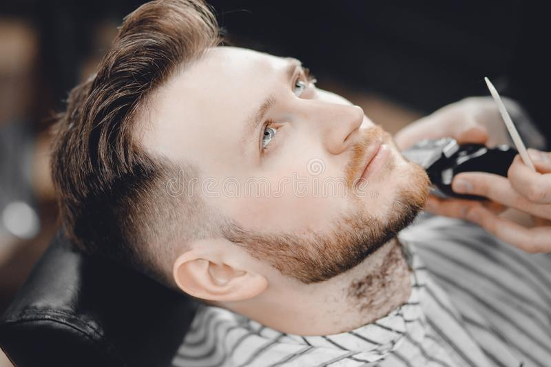 Barber shaves client beard in men barbershop with razor royalty free stock photo
