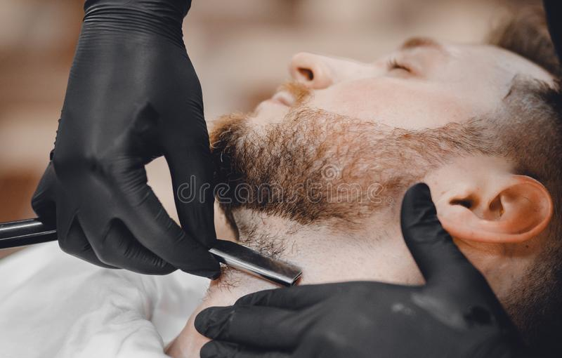 Barber shaves client beard in men barbershop with razor royalty free stock photos