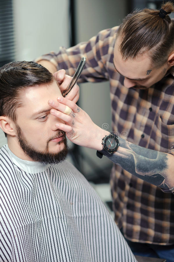 Barber shaves a client with razor royalty free stock image