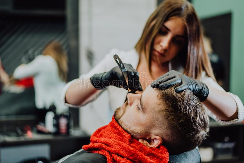 Girl hairdresser shaves his beard with a man razor royalty free stock image