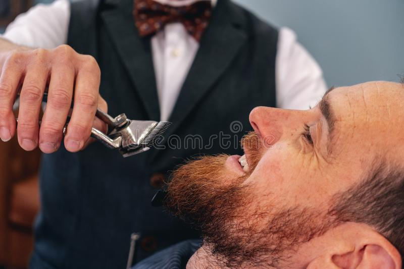 A barber shaves his client`s beard in the traditional way stock images