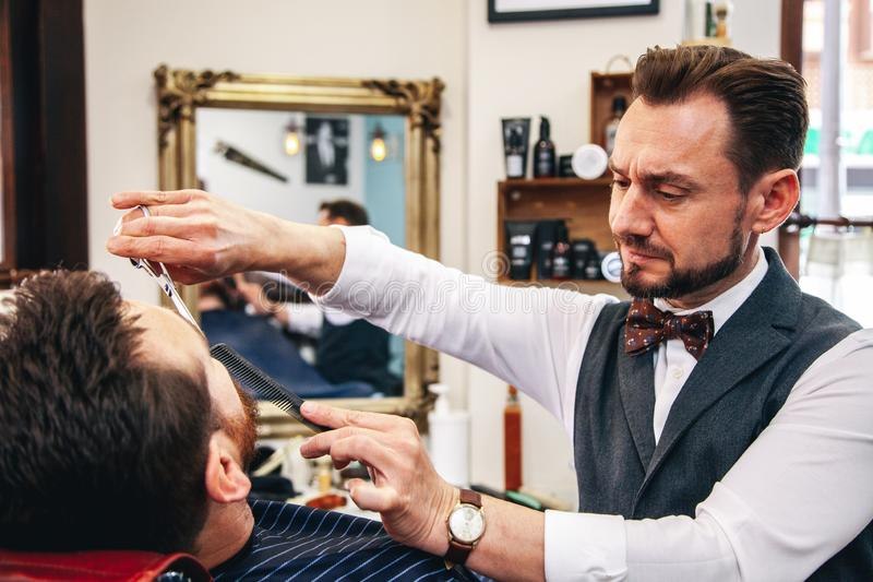 A barber shaves his client`s beard in the traditional way. royalty free stock image