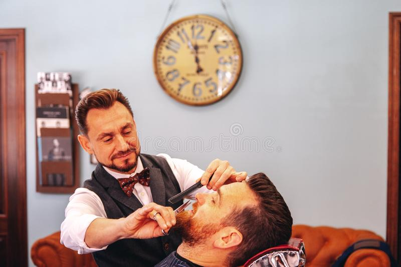 A barber shaves his client`s beard in the traditional way. stock photo